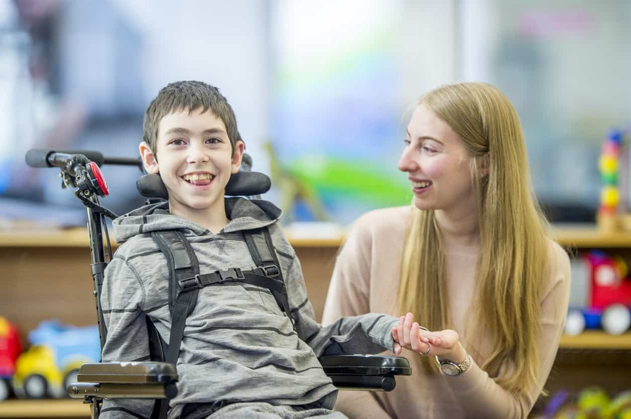 Little boy in wheelchair holds woman's hand in classroom