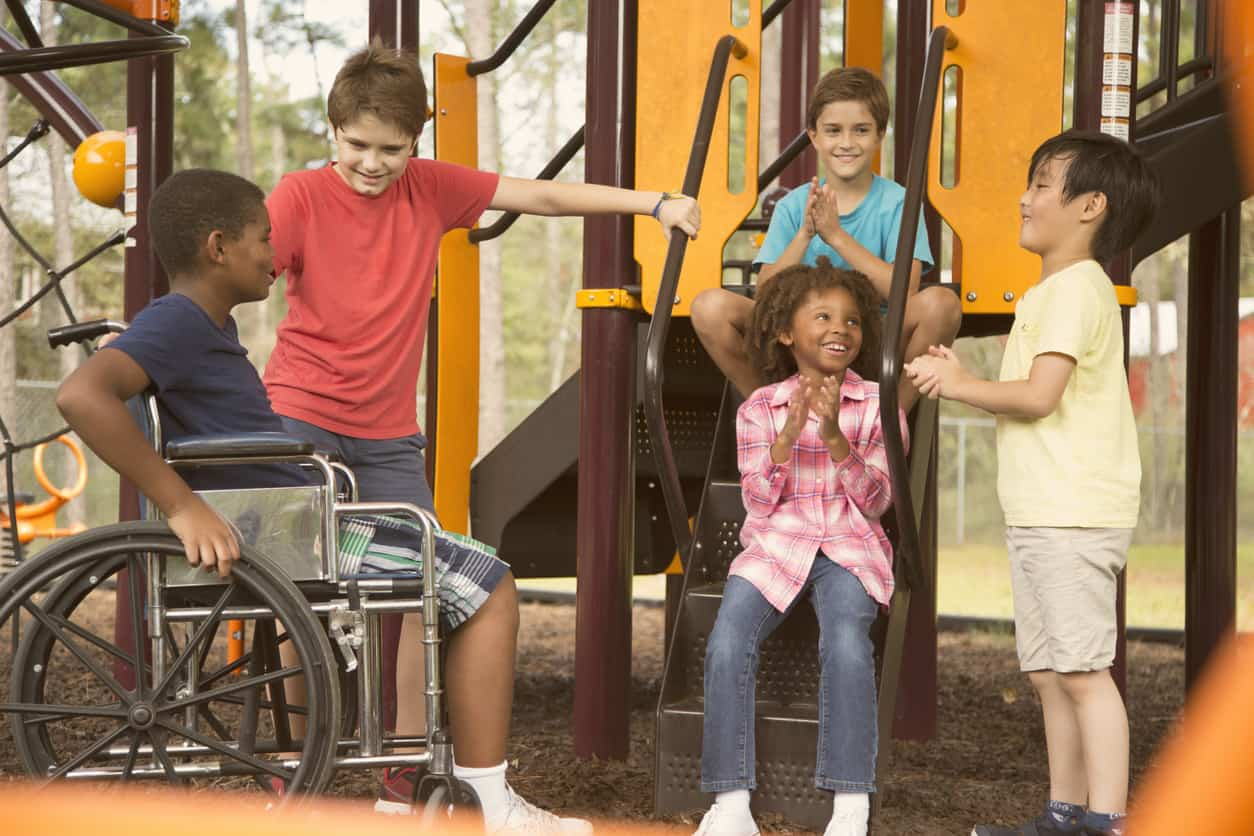 disabled child having fun with friends on the playground