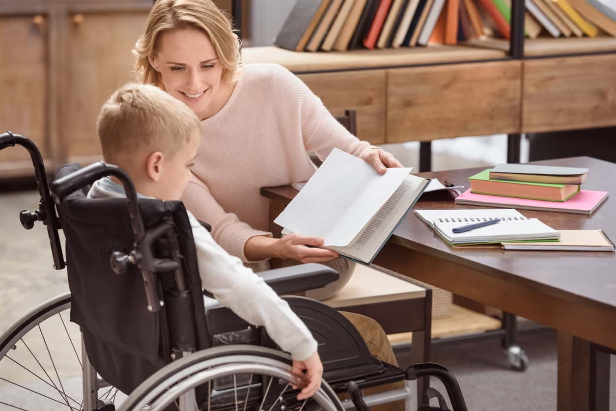 woman holds up a book for disabled child in the classroom