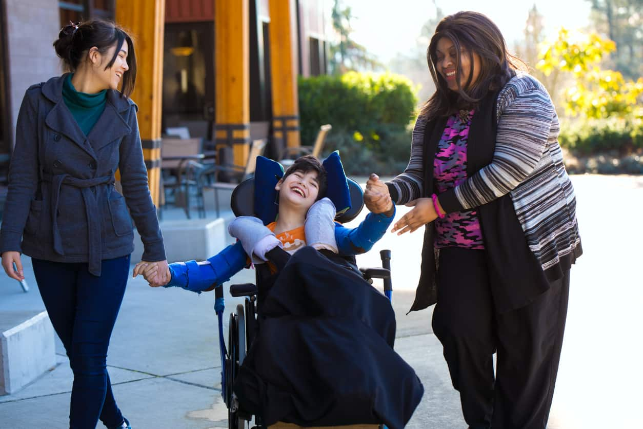 two women holding hands with little boy in wheelchair