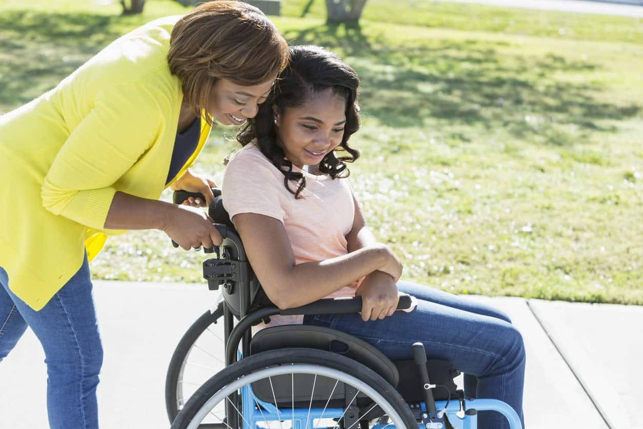 woman helps push a girl in a wheelchair down the sidewalk