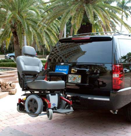 Wheelchair carrier attached to a black Chevy